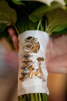 She pinned all of her bridesmaids' pins on her bouquet.