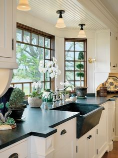bay window at sink, white cabinets with dark counter tops