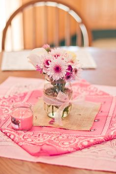 Simple pink bandanas (Michaels) with a piece of burlap on it (Amazon), a mason jar wrapped with a strip of burlap and ribbon, and some assorted flowers.  These were the table centerpieces.