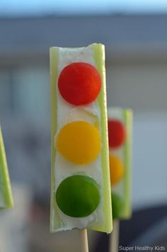 Celery filled with cream cheese and decorated with red, yellow, and green bell peppers