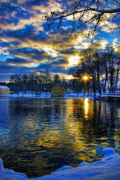 This picture is different because it was taken in the winter and the snow contrasts with the dark water and the branches with the setting sky.