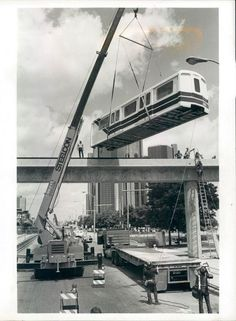 The first People Mover car is lifted onto the tracks in the summer of 1985. - Imgur
