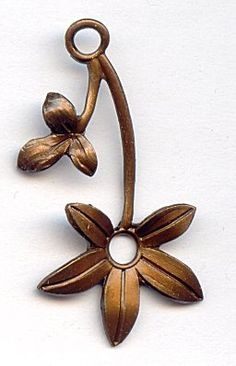 59135  Vintage Open Flower Drop  What a dainty little flower!  This open flower drop has an opening in the center of the flower and also one at the top of the drop.  The curved stem gives the charm a feeling of movement or twisting.  Use multiples of this charm in a bracelet or necklace or highlight this drop in a pair of earrings.  Can be used with our vintage brass rivets.
