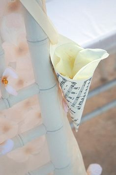A cone made of a music sheet, filled with rose petals, is attached to each guest's chair at the ceremony, ready for tossing. Click to see more ideas.