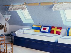 Boat oars make whimsical curtain rods, and nautical flags make the room seaworthy. So cute.