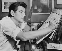 Leonard Bernstein seated at piano, making annotations to musical score, 1955.