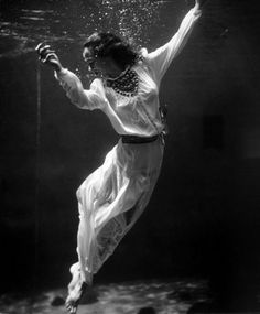 Toni Frissell - A fashion model underwater in the dolphin tank at Marineland, Florida circa 1939. S)