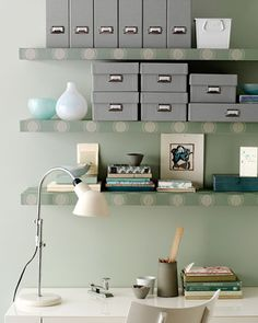 Wallpapered shelves and grey storage boxes in this home office