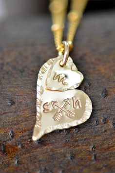 A dainty personalized gold heart has prettily hand-crafted details.
