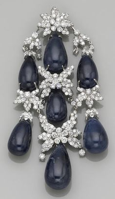 A sapphire, diamond and eighteen karat white pendant designed as a cascade of seven drop-shaped sapphire beads with round brilliant-cut diamond floral motif accents; estimated total sapphire weight: 245.00 carats; estimated total diamond weight: 8.75 carats; length: 4in.