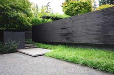 black walls, landscape architecture, green garden, ornamental grasses, black fenc
