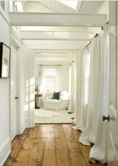 wide plank pine floors, billowy white curtains, white furniture