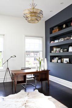 Dark built-in shelves, wood desk, chandelier (Michelle James via Remodelista)