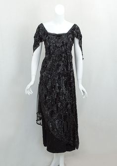 Sequined tulle/satin dinner dress, c.1918 $1200. The black satin under dress has two layers of sequined tulle on the skirt. The sequined tulle over dress is open to the waist on one side, revealing the layered underskirt. The waist has a wide inner petersham. The dress closes in back with hooks and snaps. When you see the elaborate overlapping of layers that require snaps, you will understand why a lady needed the help of a maid in order to dress.