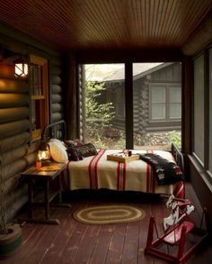 The screened-in porch off this log cabin has cozy, rustic appeal.