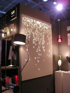 Use a canvas, apply stickers, decal, etc., and spray paint. Remove Decals; hang white lights behind it.