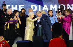 Prince Charles kisses the hand of  Queen Elizabeth II, Mummy on stage as British singers Paul McCartney (3rd from right), Elton John (right) and other performers look on after the Jubilee concert at Buckingham Palace in London, on June 4, 2012.