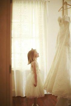 Flower girl looking at brides wedding dress