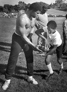 Omaha Central grad and former Chicago Bears great Gale Sayers hands off the ball to Mike Baxter, 13, at Adams Park in Omaha. The free football clinic ran two days in the summer of 1972. THE WORLD-HERALD