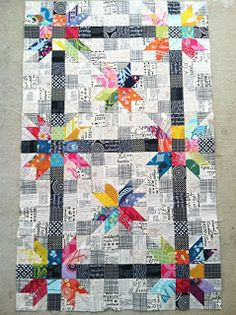 ivory and black prints quilt. A nice change from the solid backgrounds behind nice colorful scrappy stars.