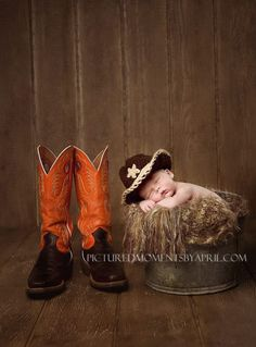newborn baby boy wearing a cowboy hat posed in an antique bucket next to daddys cowboy boots