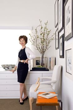 barbara barry -wall art display for the office, polka dot chair and lucite desk with out sliding ladder up top and wallpaper backed built in
