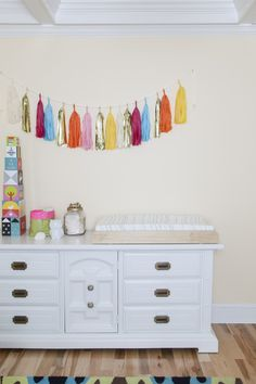 The tissue tassel garland over the changing table is fun decor, but also something for baby to watch during diaper changes! #nursery