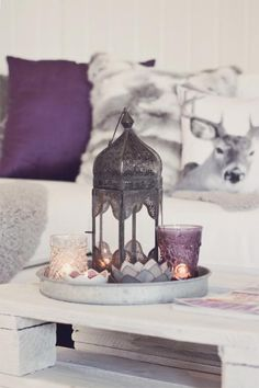 Beautiful coffee table styling. Morrocan lantern, candles, whites and purples. <3