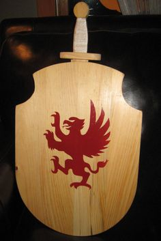 Wood shield and sword. Locally hand crafted.  Leather straps and sword holder on back.  Different emblems to choose from. Very beautiful woodwork! 2013 Faire
