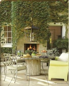 Love this outdoor pedestal table and ivy covered fireplace