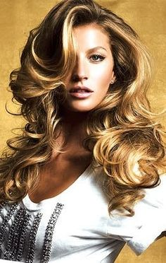 Long brown voluminous loose curly waves with blonde highlights and side swept fringe