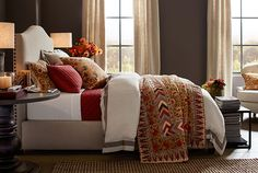 Brighten you bedroom with deep reds and patterned quilts.