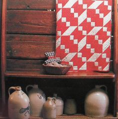 Old Wooden Bench...old crock jugs...vintage red & white quilt.
