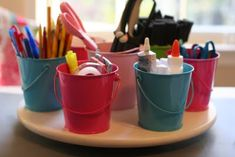 This is AWESOME. You buy a lazy susan and glue on little buckets from the dollar store. It's a super cute and easy way to store craft supplies or even napkins and silverware at the kitchen table.