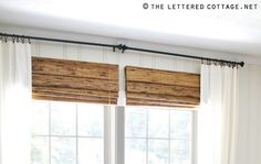 add a bamboo shade that is hung closer to the curtain rod than the window to give the illusion of a tall window. I would have gone with one large bamboo curtain for this.