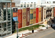 """22 giant books adorn the side of the Kansas CIty Central Library's parking garage. The """"bookshelf"""" of 25-foot tall tomes include classics such as Charlotte's Web, O Pioneers!, and To Kill a Mockingbird."""