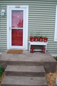 Bright front door makes a bold but inviting statement. Create your own house number pots from simple terra cotta versions.