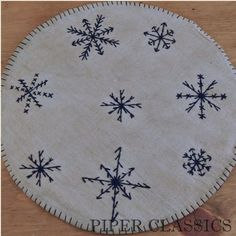 "Candle mats are designed as a decorative trivet for your candle pans or jar candles, protecting your surfaces as well as providing an attractive accent. The large mats also work great under lamps or centerpieces. This primtive hand embroidered mat is tea-dyed and reverses to plain homespun. Snowflake Candle Mat - Large; 14"" in diameter. #snowflake placemat #winter decor #snow themed"