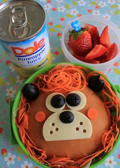 Sandwich made using a hamburger bun.  The lion's mane is made from carrots, & his face is made from cheese, olives, & carrots for his cheeks.