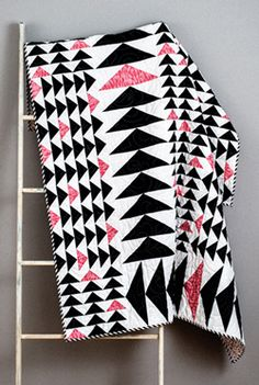 Goose Chase from Quilty July/August is a quilt pattern featuring flying geese quilt block units in black and white fabrics with a touch of pink.