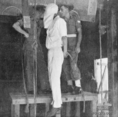An unidentified British officer (left) and sergeant (right) standing on a platform immediately below the trapdoor and gallows, next to the body of a Japanese war criminal who has just been executed by hanging on the gallows at Changi Gaol. His hands tied behind his back and he wears all white, including a hood over his head. 1946.
