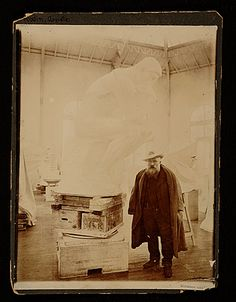 "Auguste Rodin in his studio next to ""The Thinker"""