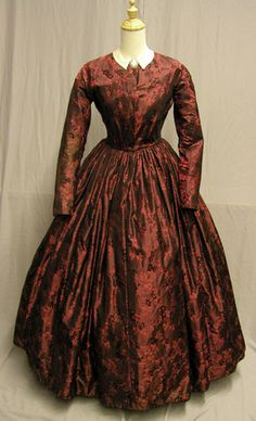 1850's Brocade dress made of rich brocade of deep red and black.  Left sleeve is actually 9-10 pieces put together and there has been a piece added to the back to enlarge the dress.  The collar is actually 2 cuffs sewn together to make a collar. Bust 34, Waist 26, skirt length 37 and 139 inches at bottom.