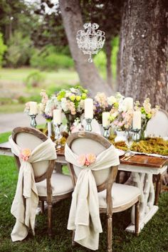 lovely.... VIntage chairs with Blush and Cream flowers, candles, and moss centerpiece! wedding tables, sweetheart table, table settings, wedding ideas, shabby chic, chair sashes, wedding chairs, vintage inspired, outdoor weddings