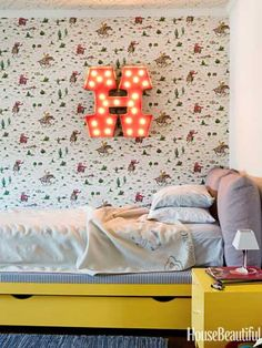 Boy's bedroom with Cath Kidston's cowboy wallpaper and a vintage circus-sign light.