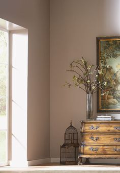 Complementary colors can add interest to a decor. The mauve color in this hallway feels interesting, but at home, in this space because of the way it complements the light greens in the large painting. By picking a shade on the opposite end of the color wheel, the wall color feels at home with this painting.