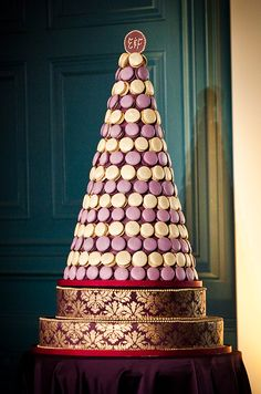 An luxurious macaron pyramid features gold and purple treats- ideal for an elegant, formal wedding.