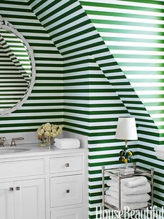 "Used horizontally on slanted walls, the powder room's green stripe wallpaper by Rose Cumming is ""a total Dorothy Draper move,"" Sommers says."