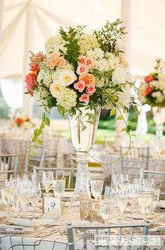 A floral centerpiece of variegated roses and white hydrangeas is complete with a clear vase.