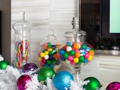 The combo of colorful candies in clear-glass apothecary jars gives this mantel a whimsical, youthful vibe.  #HolidayHouse